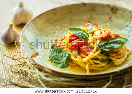Home made prosciutto and basil on a wooden board in the Italian style - stock photo