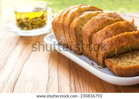Home made sliced banana cake on white plate with a glass of tea and garden view background. - stock photo