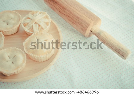 Home made sweet pie and bakery concept: Closeup shot of fresh baked sweet pastries and coffee on wire racks on a rustic wood kitchen table with green garden background. - Vintage light.