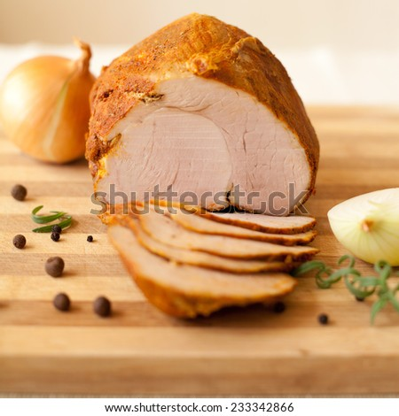 Home-made whole boiled chicken ham prepared by polish butcher. Presented on a wooden desk-board. Part of ham is cut to slices, shown with black pepper grains and onions - stock photo