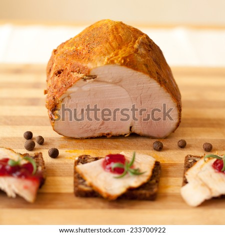 Home-made whole boiled chicken ham prepered by polish butcher. Presented on a wooden desk-board. Part of ham is cut to slices, shown with cranberries marmalade. - stock photo