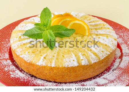 Home made whole testy orange cake, on red plate - stock photo