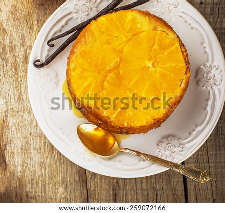 Home made whole testy orange cake with honey glaze and natural vanilla on wooden background. Selective focus. top view - stock photo