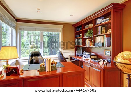 Home office luxury interior with grey walls and wood. Furnished with wooden desk and leather chairs.