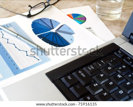Home office with  laptop and pen on the investment charts. - stock photo