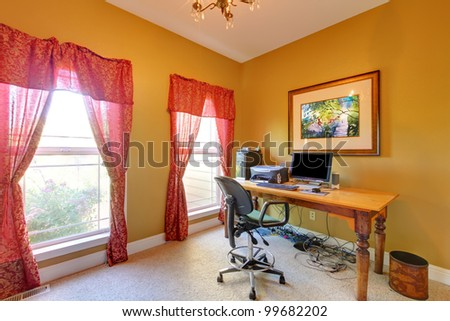 Home office with lots of wires under the table and gold walls. - stock photo