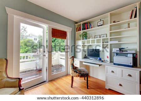 Home office with white open shelves, hardwood floor and blue walls. - stock photo