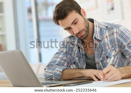 Home-office worker taking notes on paper - stock photo