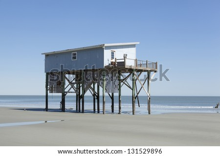 home on stilts undercut by storm waves - stock photo