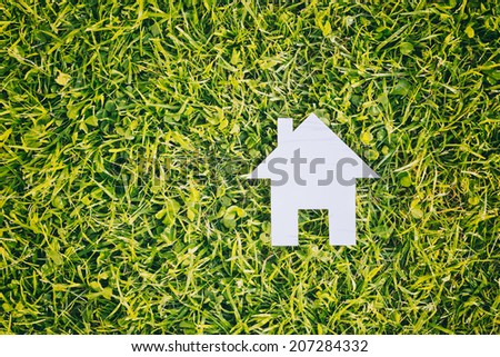 Home or house concept - white cutout building over green grass with copy space. Top view. - stock photo