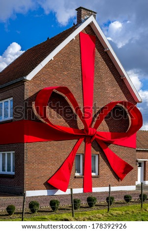 home packed like a present, with a red ribbon strapped around it - stock photo