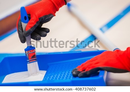 Home Painting Concept. Paint and White Paintbrush Worker Preparing for the Painting. - stock photo