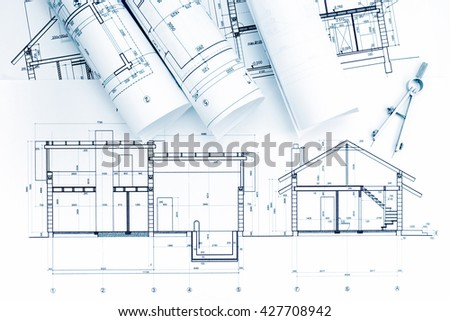 home plans and blueprint rolls with drawing compass on desk - stock photo