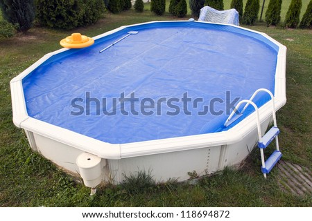 Home pool covered with solar cover. - stock photo