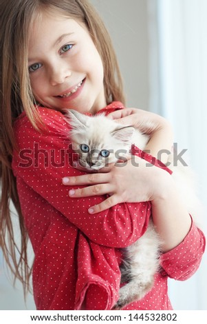 Home portrait of adorable child with small kitten - stock photo