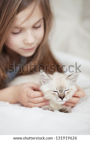 Home portrait of adorable child with small kitten resting on a soft sofa - stock photo - stock-photo-home-portrait-of-adorable-child-with-small-kitten-resting-on-a-soft-sofa-131919626