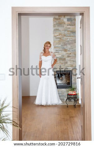 home portrait of beautiful blonde smiling bride dressed to white clothe - stock photo