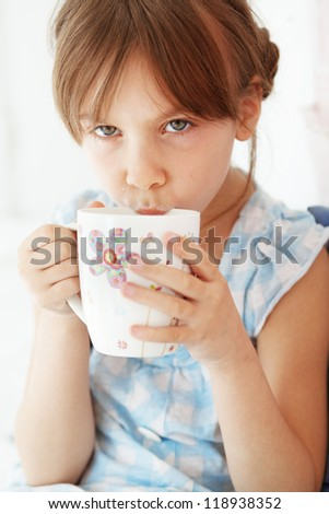 Home portrait of child drinking milk in bed