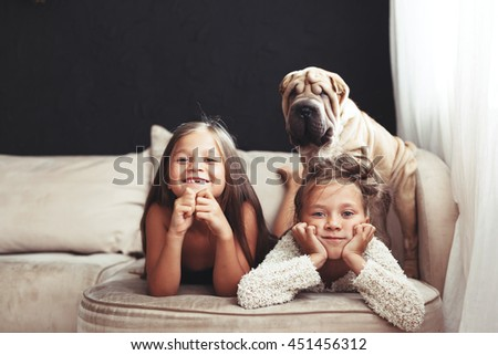 Home portrait of two cute children hugging with puppy of Chinese Shar Pei dog on the sofa against black wall - stock photo