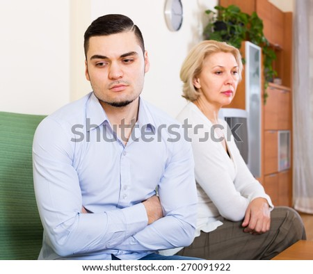 Home quarrel between mature woman and her young handsome boyfriend  - stock photo