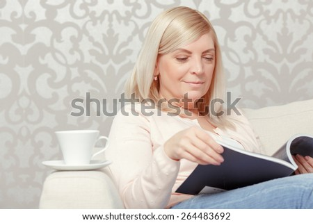 Home relaxation. Close up of an attractive middle aged woman reading a magazine and drinking coffee at the home sofa - stock photo