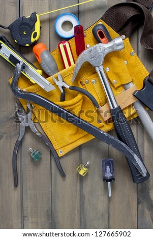 Home renovation in progress. Tool belt with various tools against wooden surface, add your text. - stock photo