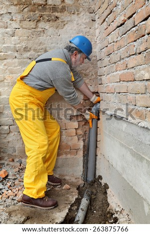 Home renovation, plumber fixing sewerage pipe at construction site - stock photo