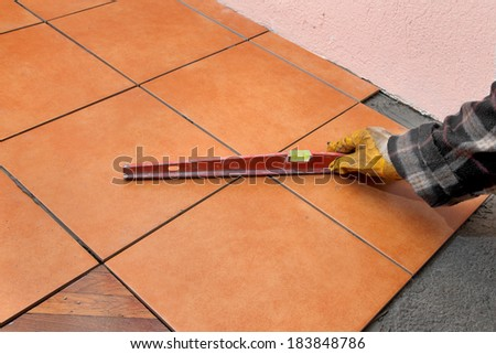 Home renovation, worker leveling tiles with level tool - stock photo