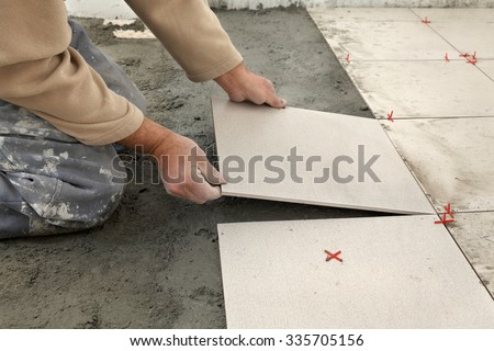 Home renovation, worker placing tiles to floor, using cement mixed with sand - stock photo