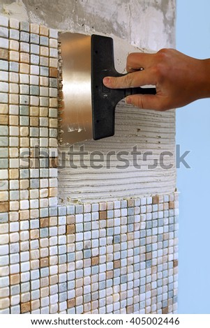 Home repair: installing the mosaic tile on the wall. / A worker covers the wall with adhesive using a notched trowel. - stock photo