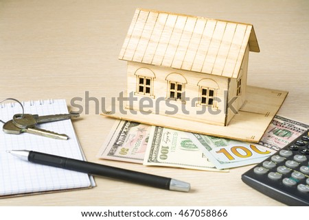 Home savings, budget concept. Model house, pen, calculator and coins on wooden office desk table.