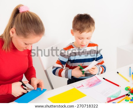 Home school education; mother and her son cutting colored paper; young woman helping boy to do homework; mom homeschooling her little boy; mother teaching her preschool son to cut by scissors