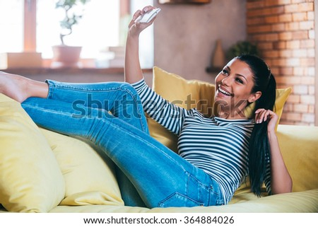 Home selfie. Beautiful young woman making selfie by her smart phone and smiling while lying on the couch at home  - stock photo