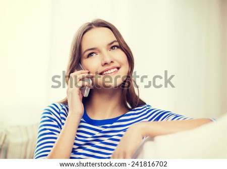 home, technology and communication concept - smiling teenage girl with smartphone sitting on couch at home - stock photo