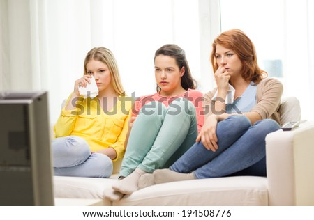 home, technology and friendship concept - three sad teenage girl watching tv at home - stock photo