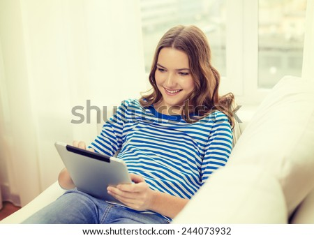 home, technology and internet concept - smiling teenage girl lying on the couch with tablet pc computer at home