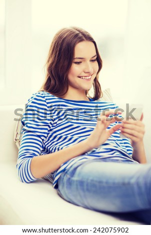 home, technology and internet concept - smiling teenage girl with smartphone lying on couch at home - stock photo