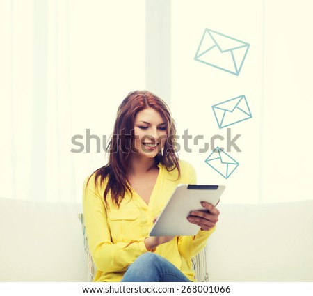 home, technology and internet concept - smiling woman sitting on couch with tablet pc computer at home - stock photo