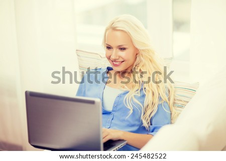 home, technology and internet concept - smiling woman sitting on the couch with laptop computer at home - stock photo