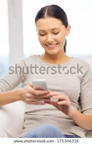home, technology, communication and internet concept - woman sitting on the couch with smartphone at home - stock photo