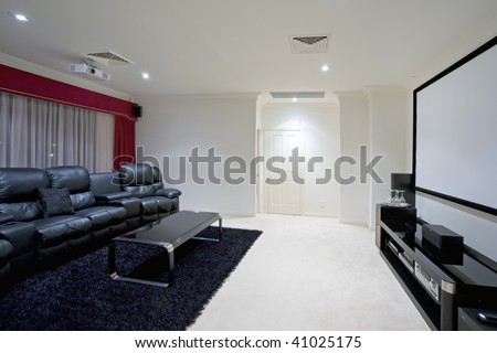 home theater room with black leather recliner chairs, red curtains, black rug and table with wine glasses and projector screen on wall - stock photo