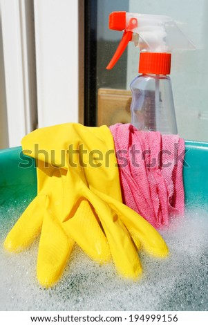 home window washer set - rubber glove, wet cloth, spray cleaner bottle, soapy water in green basin on sill - stock photo