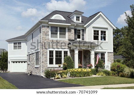 Home with stone front and covered entry - stock photo