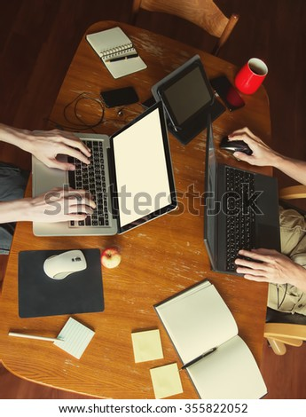 home Workspace. Freelance Family. Teamwork. Desktop table, laptop, tablet, typing keyboard hands, coffee, apple, headphones, smartphones, paper and pen - stock photo