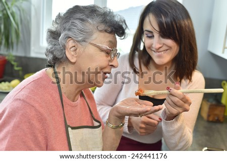 Homecare cooking dinner for elderly woman - stock photo