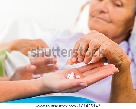 Homecare nurse helping elderly lady to take her daily medicine. - stock photo