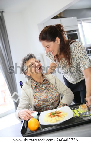 Homecarer preparing lunch for elderly woman  - stock photo