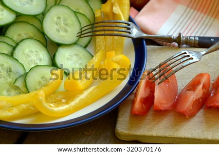 Homegrown cut tomato, pepper and cucumber on rustic table - stock photo
