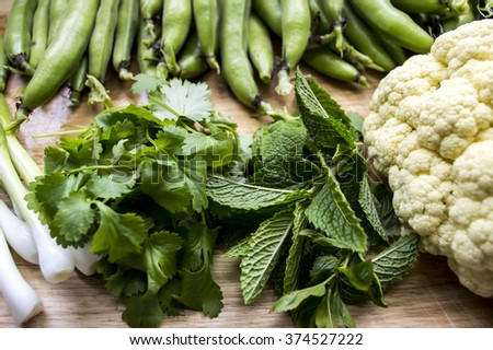 Homegrown vegetables on wooden chopping board - stock photo