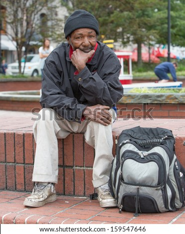 Homeless african american man sitting outdoors with backpack. - stock photo